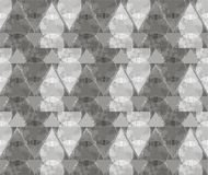 Abstract ornament from gray triangles and spirals. In white, gray and dark gray colors the seamless pattern on gray background Royalty Free Stock Image