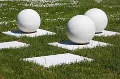 Abstract outdoor composition of white balls on bases Royalty Free Stock Image