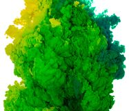 Abstract paint background color of green and yellow ink splash in the water isolated on white background. Abstract paint background colored of green and yellow stock image