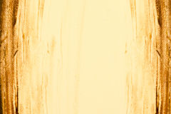 Abstract painted background in golden brown. Painted background texture with bright yellow gold in the center and brown hue vignette sides Royalty Free Stock Photo