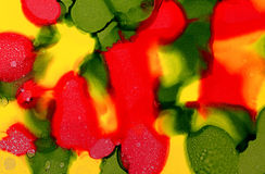 Abstract painted red drops over yellow green Stock Photos