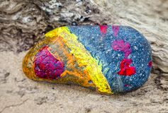 Abstract of a painted stone on a beach. Royalty Free Stock Image