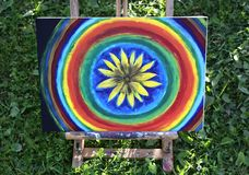 Abstract painting on canvas on easel in summer park. Abstract painting on canvas on easel in the summer park. Yellow rudbeckia flower and rainbow circles royalty free stock image