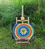 Abstract painting on canvas on easel in the summer park. Yellow rudbeckia flower and rainbow circles royalty free stock images