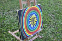 Abstract painting on canvas on easel. In the summer park. Yellow rudbeckia flower and rainbow circles royalty free stock photography