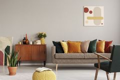 Abstract painting on grey wall of retro living room interior with beige sofa with pillows, vintage dark green armchair and yellow
