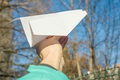 Abstract paper plane, in hand, blue sky, sun spring background. Royalty Free Stock Photos