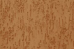 Abstract pattern with embossed from yellow stucco on a concrete wall. Surface of grooved orange wall. Texture of light brown parge. T stock image