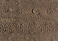 Abstract pattern of foot prints and bike tyre tracks on sand. Royalty Free Stock Image
