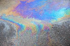 Abstract pattern of an oil or petrol slick. The abstract textured pattern of an oil or petrol slick on wet asphalt of the road royalty free stock photos