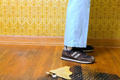 Abstract of person standing on retro 70s floor. An abstract of a person wearing sneakers and jeans standing on wooden floorboards with a retro 70s yellow Royalty Free Stock Images