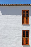Abstract photo of a building with white walls. Two, brown wooden window frames with sunny blue sky making shadows stock photography