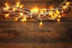 Abstract photo of Christmas warm gold garland lights on wooden rustic background. filtered image Royalty Free Stock Photography