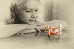 Abstract photo of cute kid looking at old wooden plane. selective focus. inspiration and childhood concept Royalty Free Stock Photos