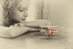 Abstract photo of cute kid looking at old wooden plane. selective focus. inspiration and childhood concept Royalty Free Stock Photo