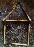 House of burnt matches against the background of ashes after a fire. Abstract photo for insurance companies and website. Insure your life and property from Stock Photo