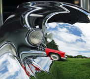 Abstract photo of a red `55 Thunderbird reflected in the chrome of an old Cadillac. Taken on a bright sunny day in a field against a blue/cloudy sky and green Stock Photo