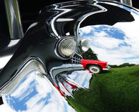 Abstract photo of a red `55 Thunderbird reflected in the chrome of an old Cadillac. Taken on a bright sunny day in a field against a blue/cloudy sky and green Stock Photography