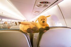Abstract conceptual photo about traveling with a child. Toy in the cabin of plane. stock photo