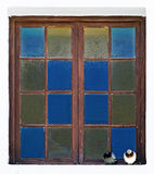 Abstract photo of two pigeons sitting on a window ledge. As though chatting about old times. Colorful window with 16 colored panes of glass stock images