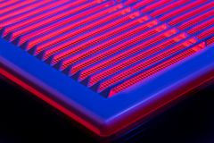 Abstract photo of a ventilation grille. Illuminated with red and blue light. Selective focus Stock Photography