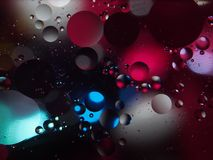 Abstract photography drops of oil on the water. Fantastic shapes of colored circles on a colorful background. Wallpaper Stock Photography