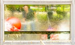 Abstract picture of a child`s game in which a ball is flushed through a basket with a water pistol, shot from the back of a glass. Pane in the target area stock photos