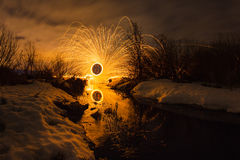 Abstract picture with trajectories of burning sparks on the surface creek at the background of spring landscape Stock Photography