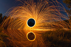 Abstract picture with trajectories of burning sparks on the surface creek at the background of spring landscape Stock Images