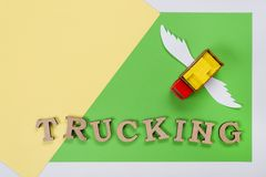 Abstract picture of a truck with wings and a word of trucking. Green background. Cargo transportation of the future Stock Photography