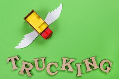 Abstract picture of a truck with wings and a word of trucking. Green background. Cargo transportation of the future Stock Photos