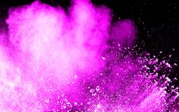 Abstract pink dust explosion on  black background. Abstract pink powder splattered on dark  background. Freeze motion of pink powder splash Stock Image