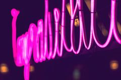 Abstract pink neon sign with blurred neon tube light background. Entertainment sign stock photography