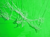 Abstract plastic oilskin pieces on green surface, Royalty Free Stock Images