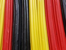 Abstract with plasticine bars in black, yellow and red color, background and texture. School material, backdrop for ads with these colors, stripes, lines and stock images