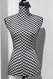 Abstract portrait of a mannequin in the mall. Female torso in a black-white cages plade isolated on grey background stock image