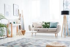 Bohemian style day room. Abstract posters hanging on a bright white wall facing a comfy sofa in a bohemian style day room interior stock photography