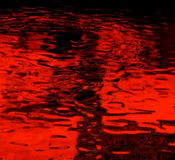 Abstract red background. An abstract green background reflections from a pool of rippling water as seen through a red filter Royalty Free Stock Image