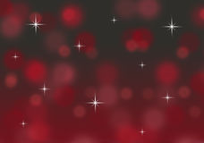 Abstract red and gold bokeh Christmas background with twinkling stars Royalty Free Stock Photos