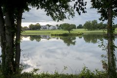 Abstract Reflection in Gold Course Water Hazard. Gray cloudy sky reflecting in water hazard on lush golf course stock image