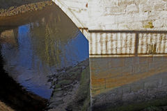 Abstract reflection of stone bridge in river Royalty Free Stock Photos