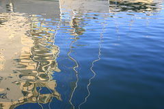 Abstract reflections of boats and buildings in blue rippled water Stock Photo