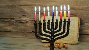 Abstract retro filtered low key image of jewish holiday Hanukkah with menorah traditional Candelabra. With glitter overlay stock video
