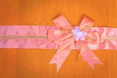 Abstract ribbon bow on fabric. Royalty Free Stock Photo