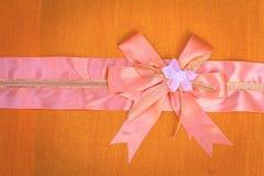 Abstract ribbon bow on fabric. Royalty Free Stock Photo