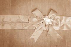 Abstract ribbon bow on fabric. Royalty Free Stock Photos