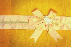 Abstract ribbon bow on fabric. Royalty Free Stock Photography