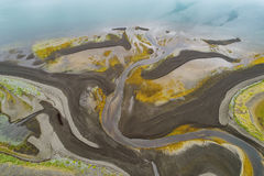 Abstract river mouth. Aerial image of a river flowing through a beach on low tide Stock Image