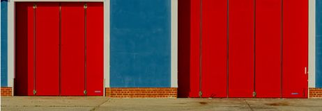 Abstract.  RNLI logo colours painted on lifeboat station. Red painted lifeboat station doors with the other RNLI Royal National Lifeboat Institution logo colors royalty free stock photography
