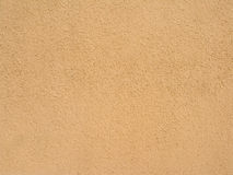 Abstract sandy brown plastered textured wall as ba. Abstract painted  sandy brown plastered textured wall as background Royalty Free Stock Photography